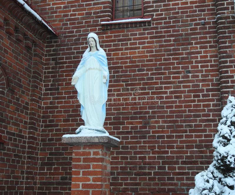 White Holy Mary near red church, Lithuania. Beautiful Holy Mary sculpture near Silute town catholic church in winter stock photography