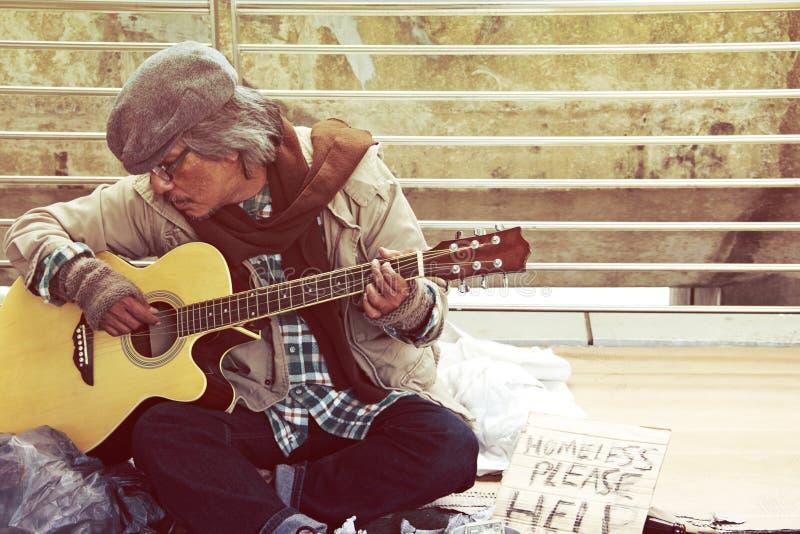 Homeless man playing guitar on walking street. Beautiful Homeless man playing guitar on street in the capital city stock photo