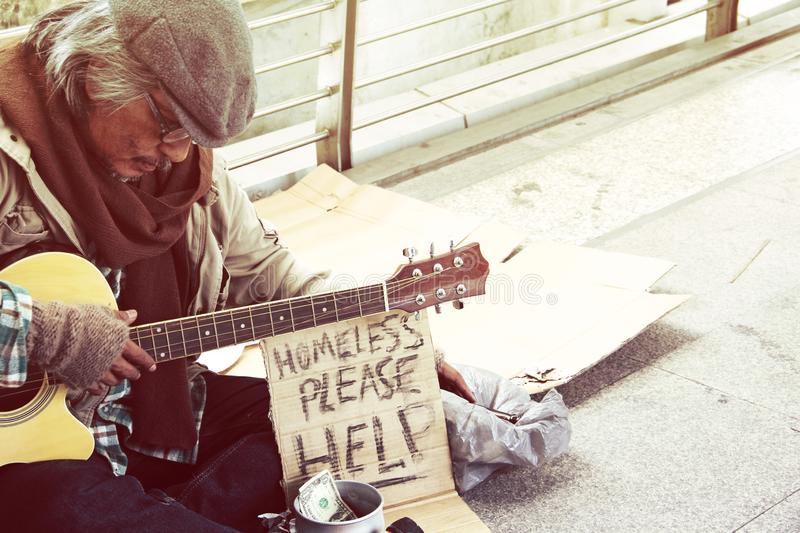 Homeless man playing guitar on walking street. Beautiful Homeless man playing guitar on walking street in the capital city stock images