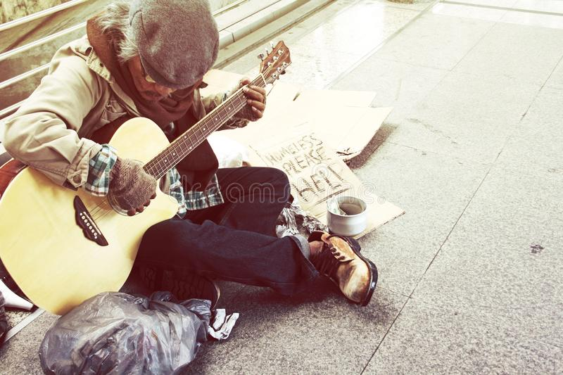 Homeless man playing guitar on walking street. Beautiful Homeless man playing guitar on walking street in the capoital city royalty free stock images