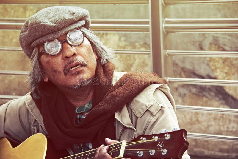 Homeless man portrait playing acoustic guitar. Beautiful Homeless man portrait playing acoustic guitar on walking street royalty free stock photo