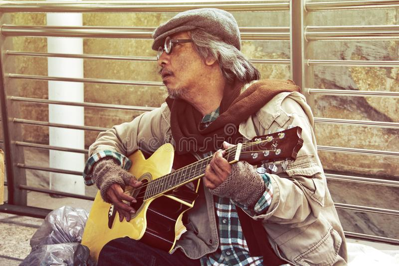 Homeless man portrait playing acoustic guitar. Beautiful Homeless man portrait playing acoustic guitar on walking street stock photos