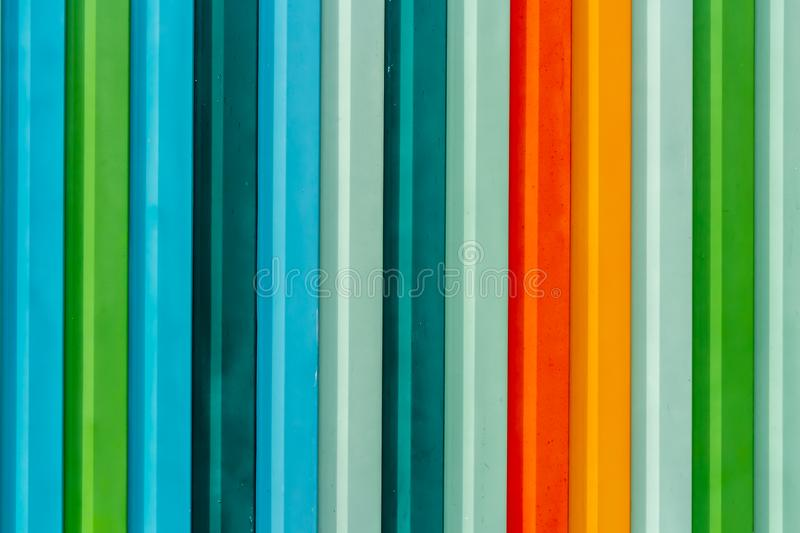 Beautiful horizontal texture of colorful red green blue orange yellow gray metal fence stock photo