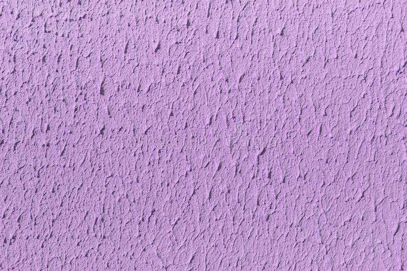 Beautiful horizontal texture of part of old concrete wall painted in Violet and white color and with holes on the photo. Beautiful horizontal texture of part of stock photo