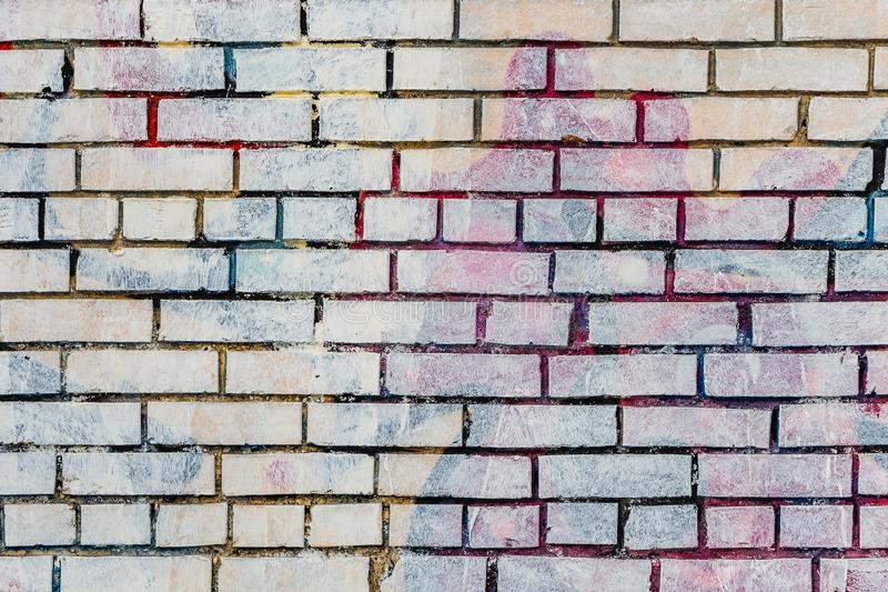 Beautiful horizontal texture of part of an old crashed brick colored wall in yellow red blue green brown hue on the photo. Beautiful horizontal texture of part stock photo