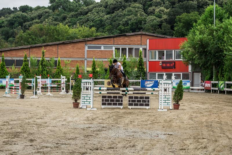 Beautiful horse and jokey in action at horse race track with obstacle equipment at hippodrome. In Belgrade, Serbia royalty free stock photography