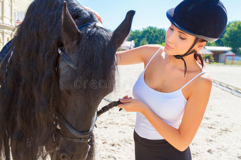 Beautiful horsewoman with a horse. Portrait of a beautiful horsewoman wearing an equestrian helmet and a white top standing near a big brown horse, looking at royalty free stock images