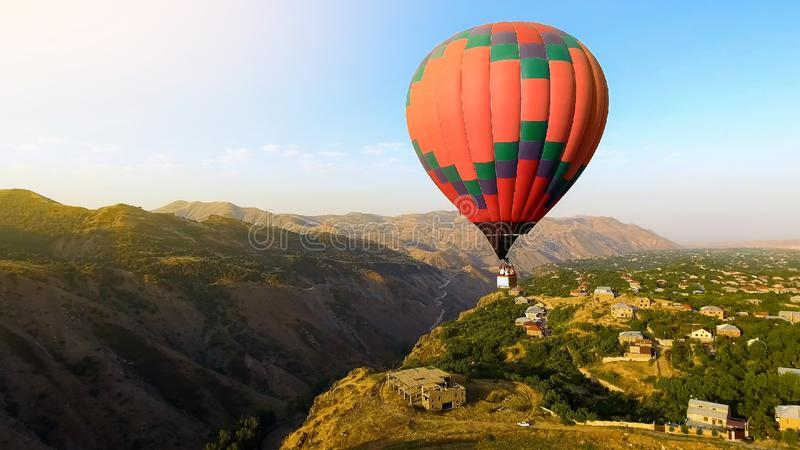 Beautiful hot air balloon flying over mountain village, Armenia aerial view. Stock photo royalty free stock photo