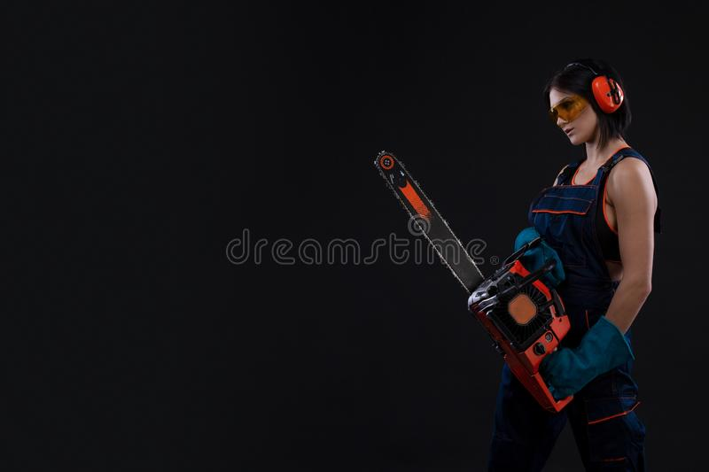 Beautiful hot woman hold a chainsaw over black background royalty free stock photo