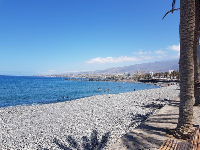 Beautiful hot sunny coastal view of stony beach with blue sea and sky stock image