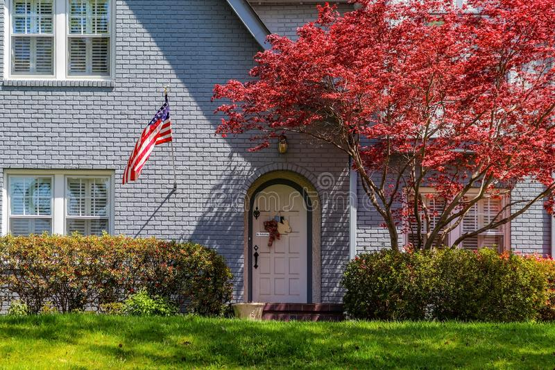 Beautiful house with arched door with Easter docoration and American flag and No Soliciting sign with Japanese Maple in front royalty free stock image