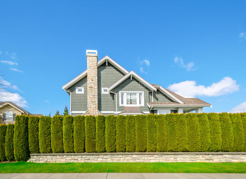 Beautiful house behind a green hedge fence stock photography