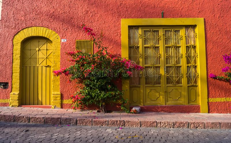 Beautiful House Exterior and Front Door Seen on a Mexico Street on yellow and red pink color royalty free stock photo
