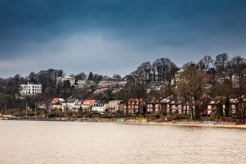 Beautiful houses and beaches on the banks of Elbe river in Hamburg on a cold end of winter day royalty free stock photography