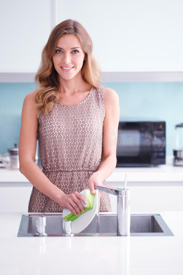 Beautiful housewife doing dishes royalty free stock photos