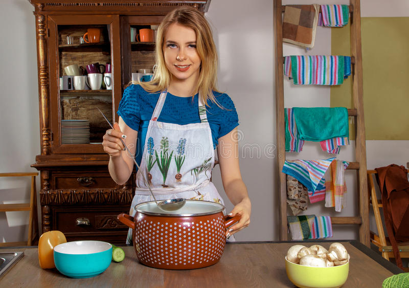 Beautiful housewife in the kitchen royalty free stock photography