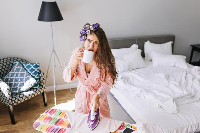 Beautiful  housewife in pink bathrobe with curler at home at ironing clothes. She drinking a tea, looks tired to camera. Beautiful  housewife in pink bathrobe royalty free stock image