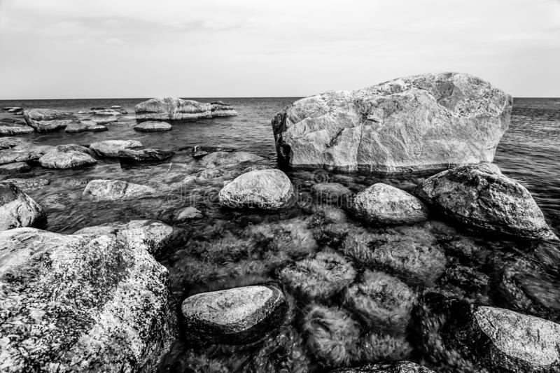 Beautiful huge stones in the sea with small stones under water overgrown with green algae in the Gulf of Finland. Black and white. royalty free stock photography