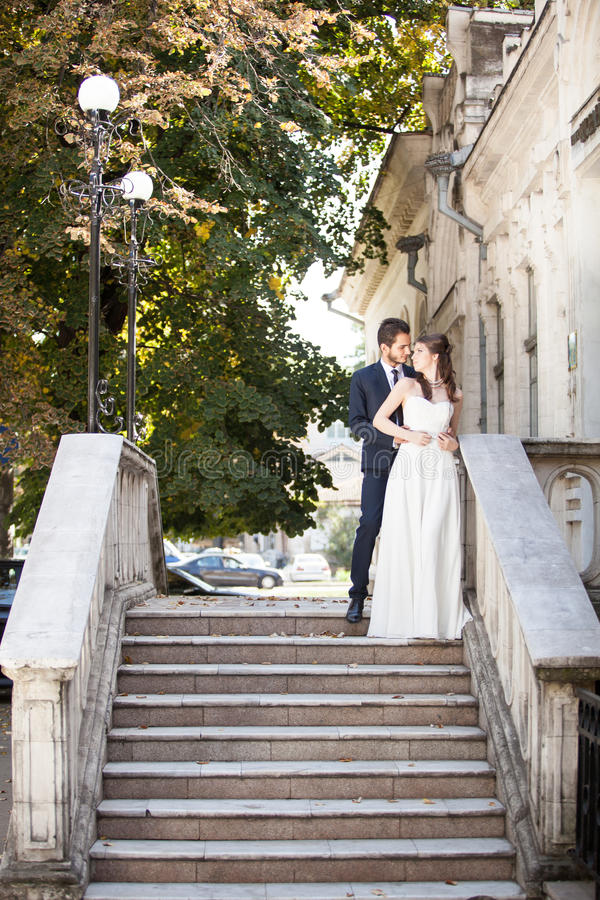 Beautiful husband and wife in wedding dress on stairs royalty free stock photo