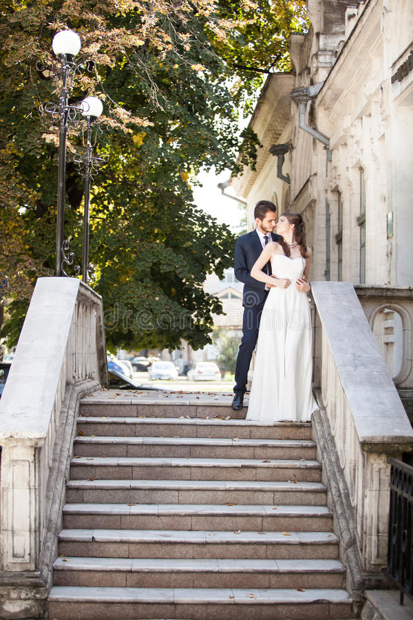 Beautiful husband and wife in wedding dress on stairs stock photography