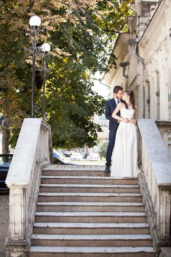 Beautiful husband and wife in wedding dress on stairs stock photos
