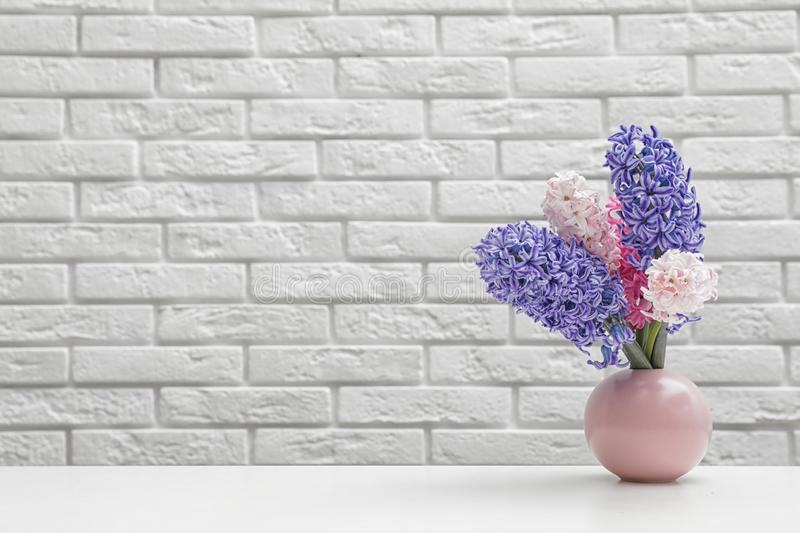 Beautiful hyacinths in pink vase on table against brick wall, space for text. Spring flowers stock image