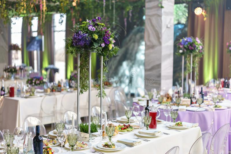 Beautiful hydrangea bouquets in vases on high stands. Flower arrangement on tables at luxury wedding reception in royalty free stock photo