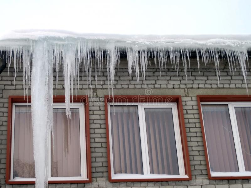 Home wall and ice icicles in winter, Lithuania stock photo
