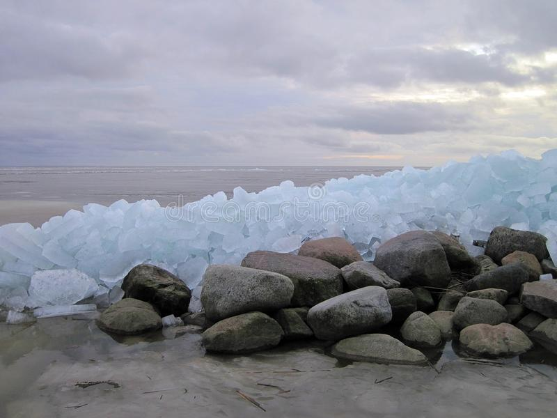 Curonian spit in winter ice, Lithuania. Beautiful ice pieces and stones and Curonian spit in winter time royalty free stock photo