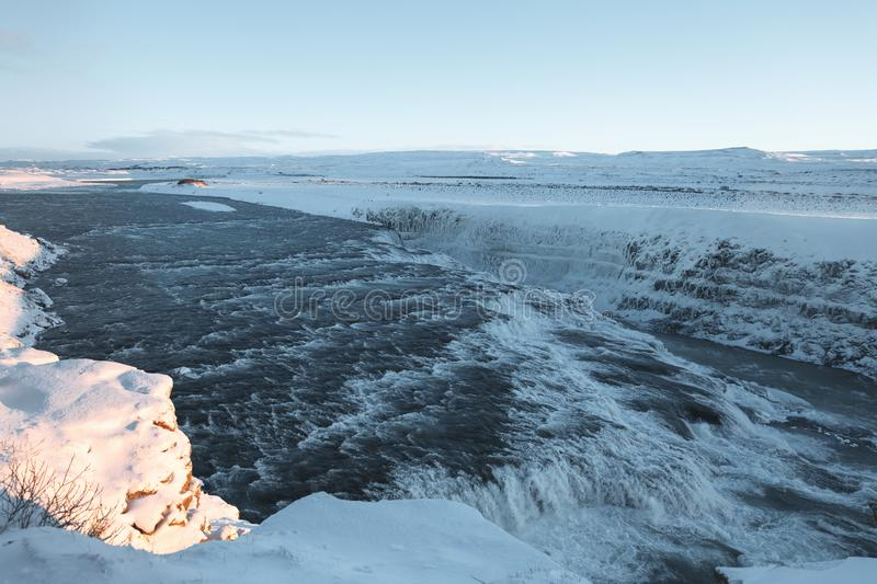 Beautiful icelandic landscape with cold river, waterfall and snow-covered. River banks stock photo