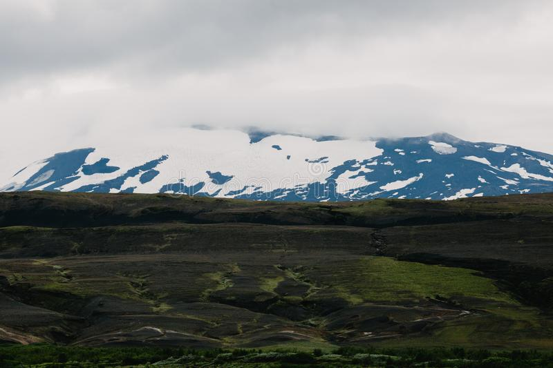 Beautiful icelandic landscape with green grass on black ground and snow-covered mountains on horizon,. Landmannalaugar, Iceland royalty free stock photos
