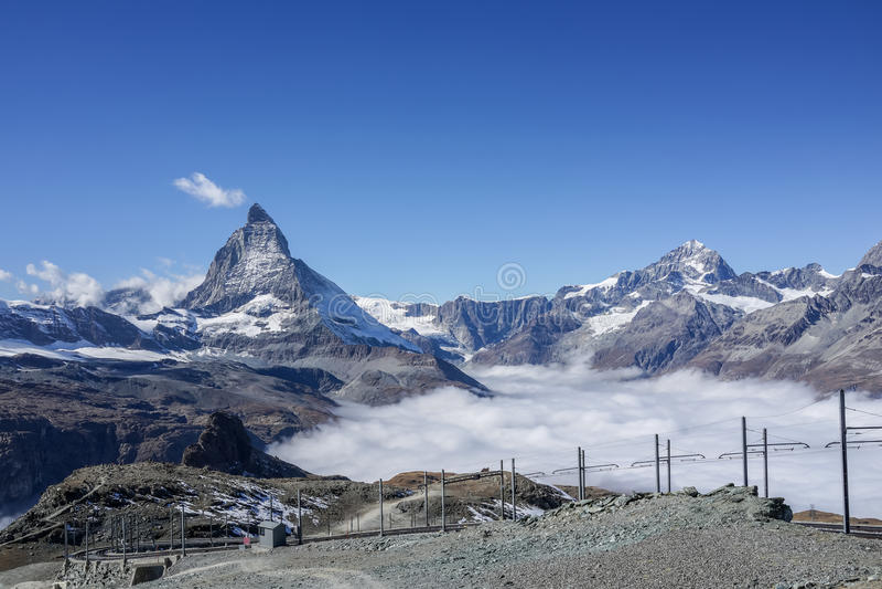 Beautiful iconic mountain Matterhorn with clear blue sky and mist below, Zermatt, Switzerland.  royalty free stock photos
