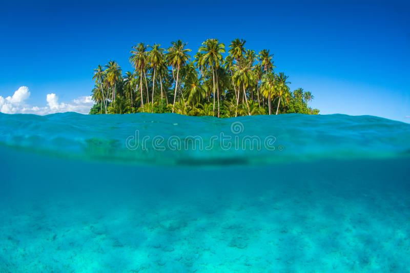 An idyllic island surrounded by the ocean in Indonesia. A beautiful idyllic little island surrounded by the ocean  in clear waters at far destination in royalty free stock photography