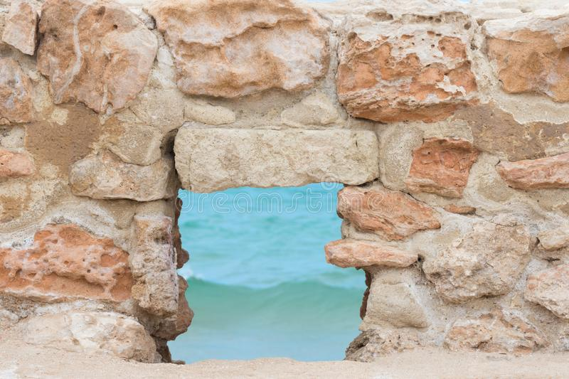 View of Turquoise Sea Ocean through Window in Ancient Fortress Stone Wall. Travel Vacation Tranquility Contemplation Freedom. Beautiful Idyllic View of Turquoise stock photos