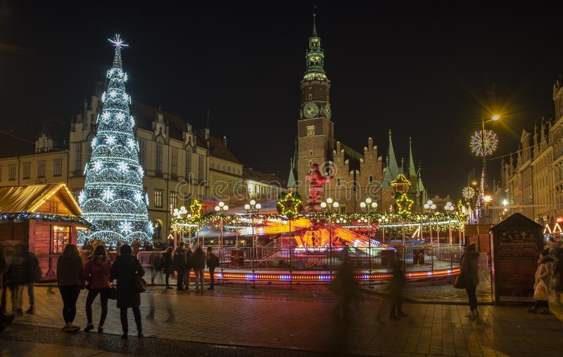 Beautiful illuminated Christmas tree and mooving carousel at Wroclaw city center. Long exposure photo. WROCLAW, POLAND - DECEMBER 12, 2019: Beautiful illuminated stock image