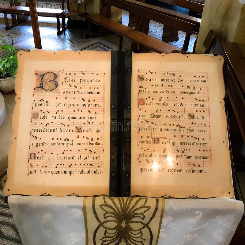 Beautiful illuminated manuscript of Gospel Beatitudes in Latin on parchment. Script of Beatitudes from Matthew on stand in Church in Galilee Holy Land stock images