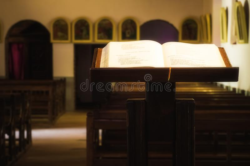 Beautiful Illuminated open christian Holy Bible placed on a wooden lectern royalty free stock photos