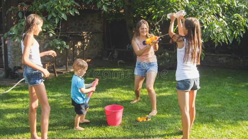 Beautiful image of happy laughing family with children having fun at hot summer day with water guns and garden hose stock photo