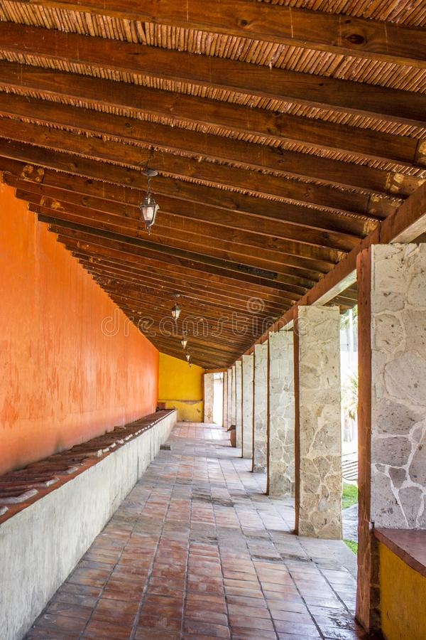 Beautiful image of the laundry room lavaderos on a long corridor with orange colored walls. With stone pillars and a wooden roof in the village of Tequila stock images