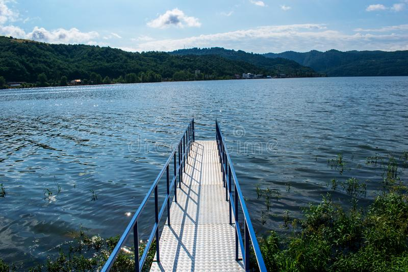 A beautiful image with a metal pontoon, across the Danube. The water is very calm and blue. A beautiful sky and mountains covered stock photo