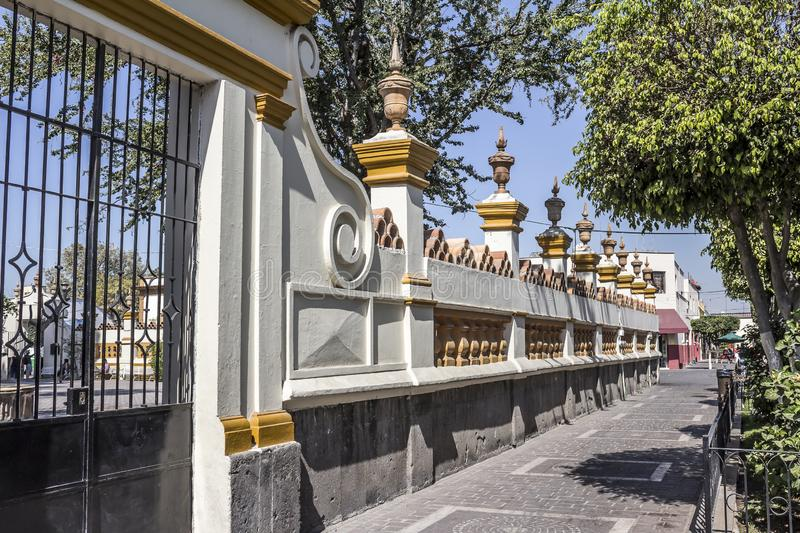 Beautiful image of the outside with its white and yellow walls and metal gate of the church of San Pedro Apóstol. On a wonderful and sunny day in Tlaquepaque royalty free stock photos
