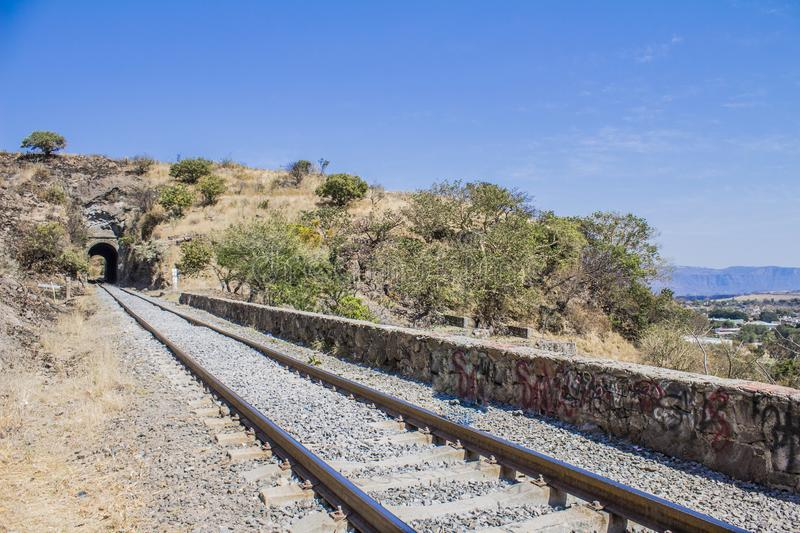 Beautiful image of the tracks of a train. That lead to the town of Tequila Jalisco Mexico with an impressive blue sky and a tunnel in the background royalty free stock images