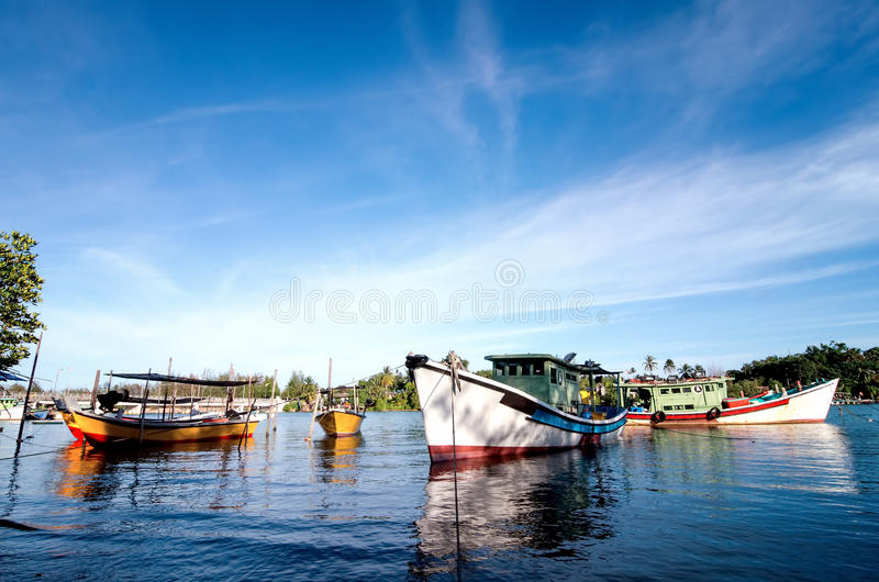 Beautiful image of traditional fishing boat with reflection and blue sky stock photos