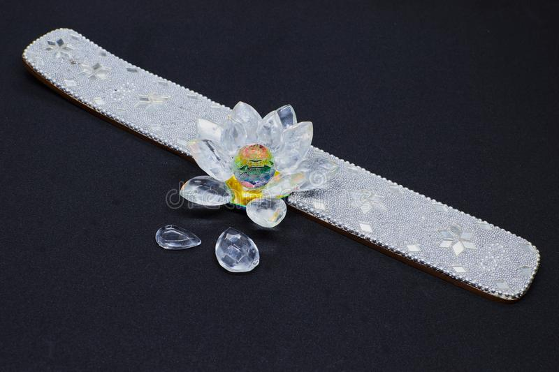 An beautiful incense holder with bright stones and flower on black background royalty free stock photography