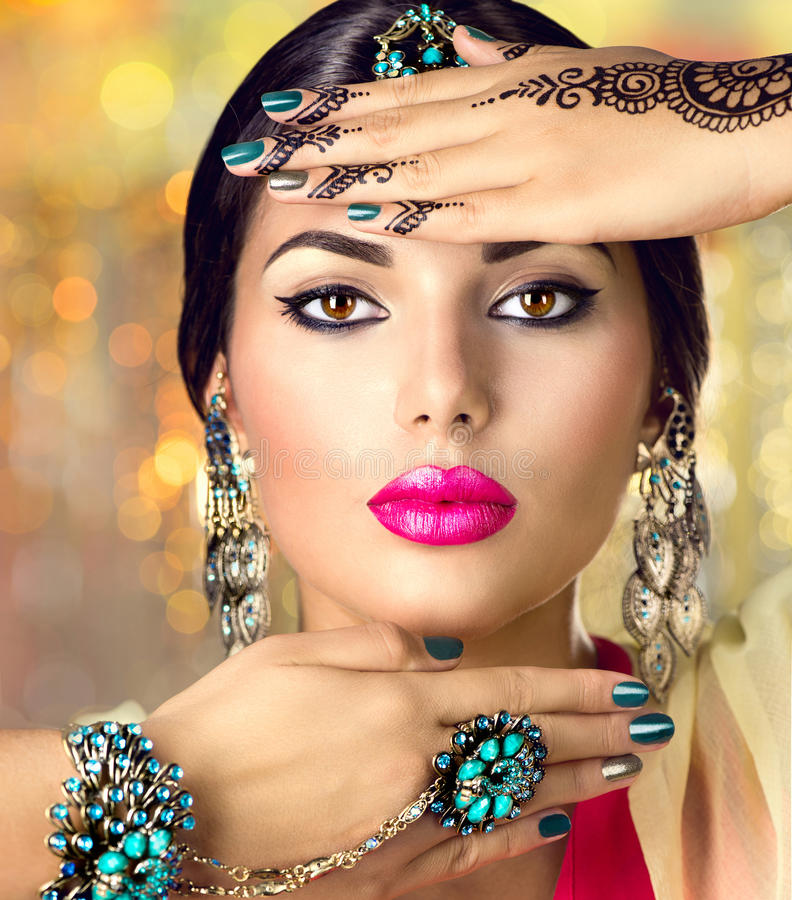 Beautiful Indian woman with black mehndi tattoo. Indian girl. With black henna tattoos on her arms and emerald oriental jewels looking in camera. Hindu model stock images