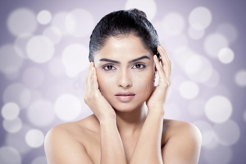 Beautiful Indian woman with healthy skin against blurred lights background. royalty free stock image