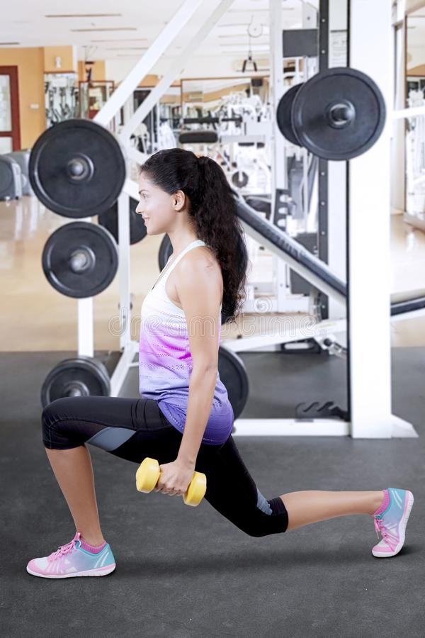Beautiful Indian woman lifting weights. In a gym royalty free stock photography