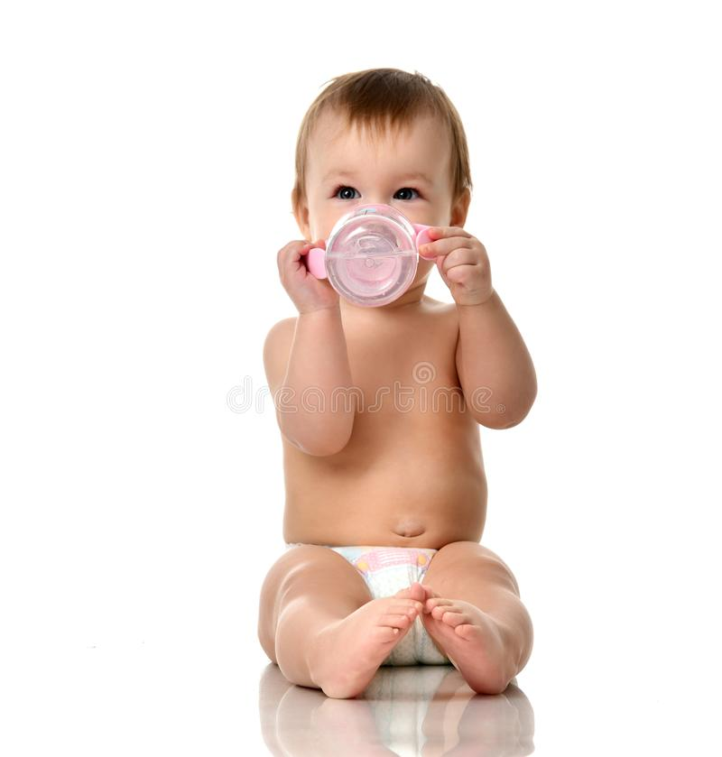 Beautiful infant baby girl toddler sitting in diaper with bottle of water stock photography