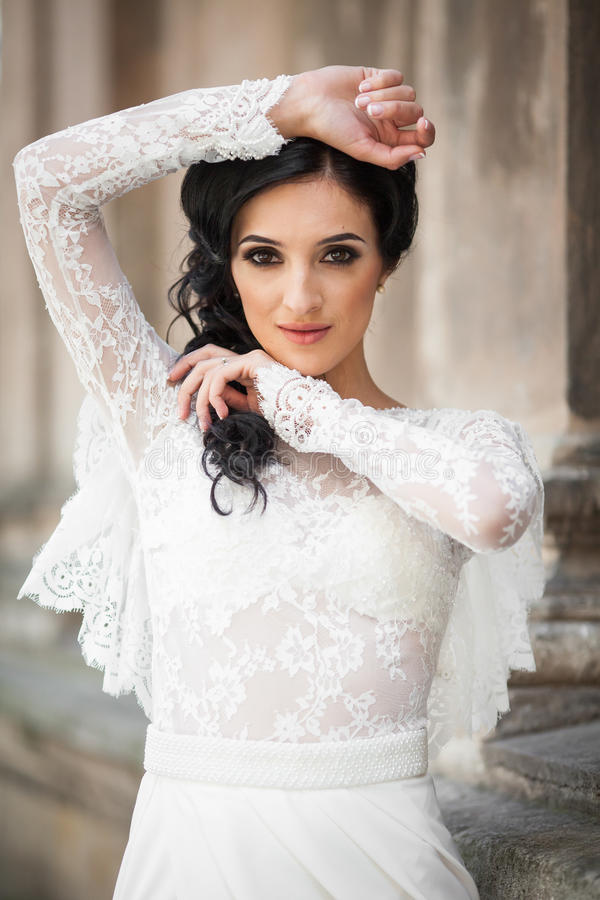 Beautiful innocent brunette bride in white dress posing near church wall royalty free stock images