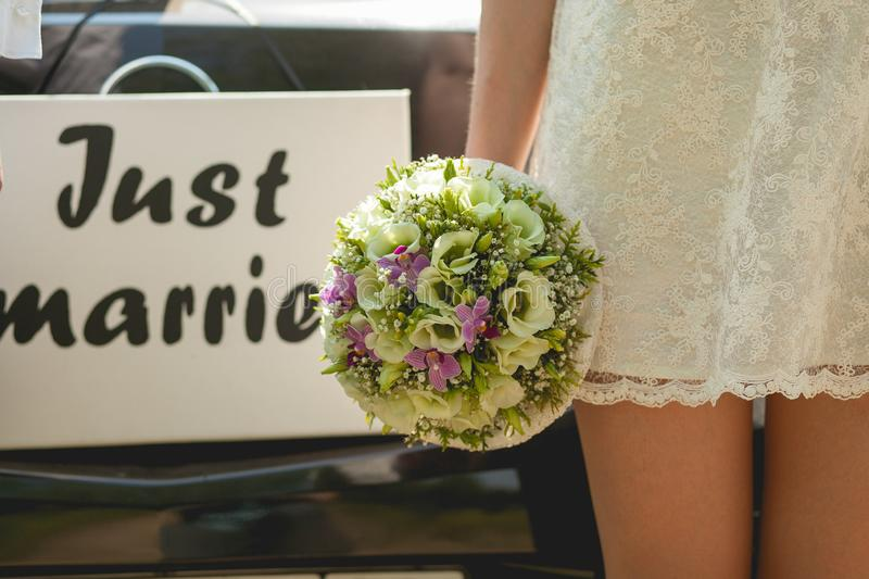 Beautiful inscription in English `just married` on the wedding photo. Next to the bride in a white short dress, holding a weddin royalty free stock images